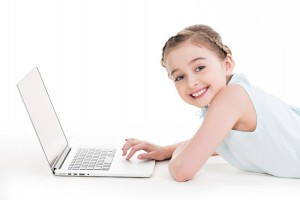 Little girl with silver color laptop.